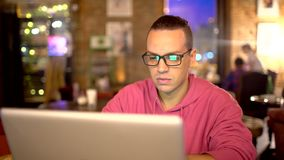 Hispanic Ethnicity Young Man using Laptop Computer at Cozy Coffee Shop. Technologies concept. man with glasses. Hispanic Ethnicity Young Man using Laptop stock video footage