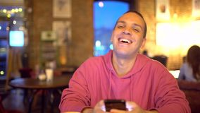 Hispanic Ethnicity Young Man using Mobile Phone at Cozy Coffee Shop. Portrait of Attractive Smiling Hispanic Ethnicity. Hispanic Ethnicity Young Man with a stock footage