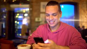 Hispanic Ethnicity Young Man with a beautiful smile using Mobile Phone at Cozy Coffee Shop. Technologies concept. Hispanic Ethnicity Young Man using Mobile stock video footage