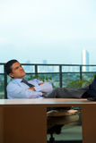 Hispanic Executive Reclining Thinking Looking Up Stock Photo
