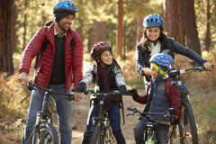 Hispanic family on bikes in a forest looking at each other royalty free stock image