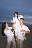 Hispanic family with daughter having fun on beach Stock Image