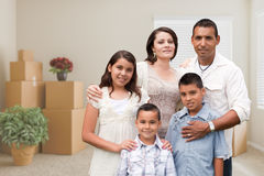 Hispanic Family in Empty Room with Packed Moving Boxes and Potted Plants royalty free stock photos