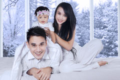 Hispanic family enjoy winter holiday at home. Portrait of happy family playing together in bedroom with winter background on the window Stock Image