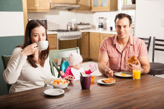 Hispanic family enjoying breakfast at home. Portrait of a beautiful Hispanic family with a baby girl eating breakfast at home Stock Photography