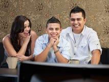 Hispanic Family Enjoying TV Stock Photos