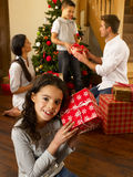 Hispanic family exchanging gifts at Christmas. Smiling Stock Photography