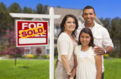 Hispanic Family in Front of Their New Home and Sign Royalty Free Stock Photo
