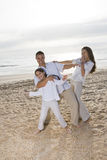 Hispanic family with girl having fun on beach Royalty Free Stock Photo