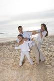 Hispanic family with girl having fun on beach Royalty Free Stock Photo