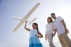 Hispanic family and girl having fun with toy plane Stock Images