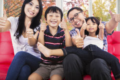 Hispanic family giving thumbs up. Joyful family sitting on sofa and giving thumbs up at camera with autumn background on the window Stock Image