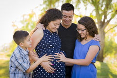 Hispanic Family Hands on Pregnant Mother Tummy Feeling Baby Kick Stock Photos