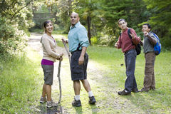 Hispanic family hiking in woods on trail stock image