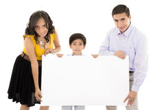 Hispanic family holding a banner and smiling. This image has attached release Stock Photos