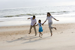 Hispanic family holding hands skipping on beach stock image