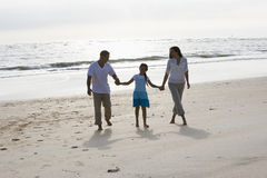 Hispanic family holding hands walking on beach Stock Image