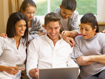 Hispanic family at home shopping online. Laughing royalty free stock photo