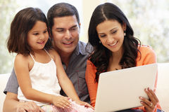 Hispanic family with laptop at home Stock Images
