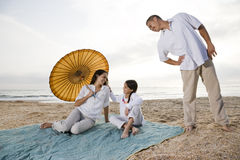 Hispanic family with little girl on beach blanket Stock Photos