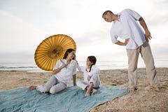 Hispanic family with little girl on beach blanket Stock Photos