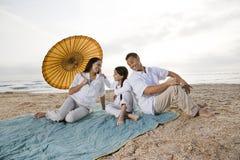 Hispanic family with little girl on beach blanket Royalty Free Stock Image