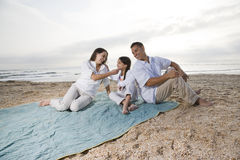 Hispanic family with little girl on beach blanket Stock Photography