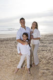 Hispanic family with little girl standing on beach Stock Images