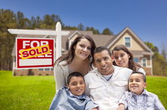 Hispanic Family New Home and Sold Real Estate Sign. Young Happy Hispanic Young Family in Front of Their New Home and Sold For Sale Real Estate Sign Royalty Free Stock Photos