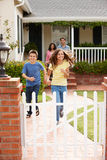 Hispanic family outside home. Running to gate Stock Photos