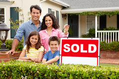 Hispanic family outside home. Happy hispanic family outside home with sold sign holding keys smiling at camera Royalty Free Stock Photo