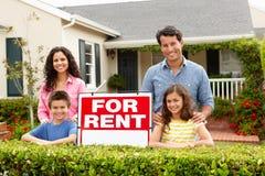 Hispanic family outside home for rent. Hispanic family outside home standing next to for rent sign Stock Photography