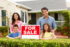 Hispanic family outside home with for sale sign. Smiling at camera Stock Images