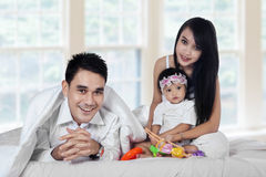 Hispanic family playing in bedroom. Portrait of happy family playing together in the bedroom at home Royalty Free Stock Image