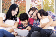 Hispanic family playing digital tablet. Young hispanic parents with their children using digital tablet at home with autumn background on the window Royalty Free Stock Photos