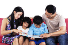 Hispanic family read book on couch Stock Image