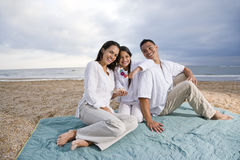 Hispanic family sitting on blanket at beach Royalty Free Stock Images