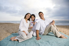 Hispanic family sitting on blanket at beach Stock Photos