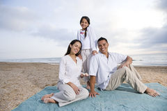 Hispanic family sitting on blanket at beach Stock Images
