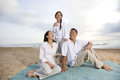 Hispanic family sitting on blanket at beach Stock Photo