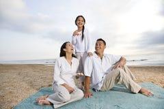 Hispanic family sitting on blanket at beach Stock Photo