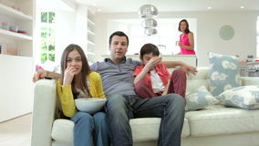 Hispanic Family Sitting On Sofa Watching TV Together