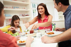 Hispanic Family At Table Eating Meal Together. Hispanic Family Sitting At Table Eating Meal Together Smiling Stock Image