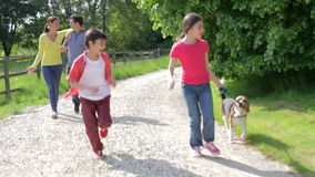 Hispanic Family Taking Dog For Walk In Countryside. Camera tracks hispanic family walking along country track as children run ahead with pet dog.Shot on Canon 5d stock footage