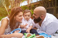 Hispanic family of three. Laying on green garden. Parents with small son Stock Image