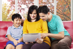 Hispanic family using digital tablet. Pregnant women with her son and husband using digital tablet together at home Stock Images