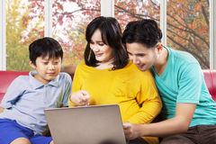 Hispanic family using laptop on sofa. Father, mother, and child using laptop computer on sofa at home with autumn tree background Stock Images