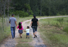 Hispanic Family - Walking Home. A young hispanic family walking the dirt and gravel road to their home in the country of 22 acres of land and a pond in Box stock photos