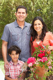 Hispanic Family Working In Garden Tidying Pots Royalty Free Stock Images