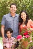 Hispanic Family Working In Garden Tidying Pots Royalty Free Stock Image